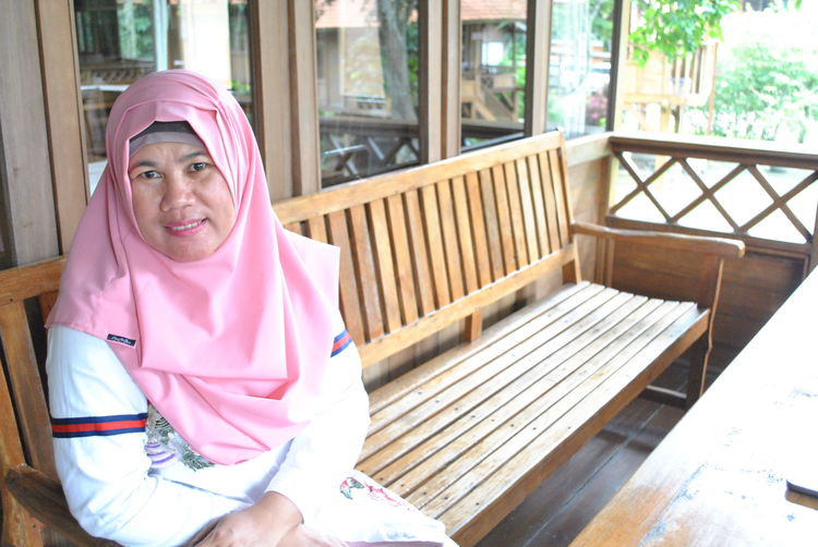 Portrait of smiling woman wearing pink hijab sitting on wooden bench