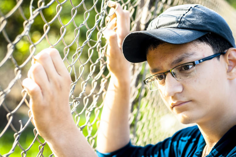 Close-up of thoughtful boy by fence