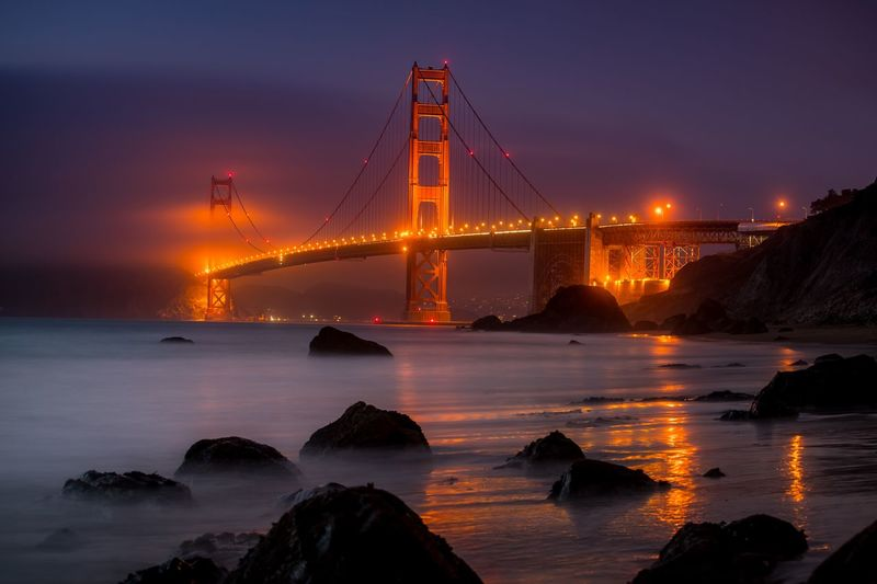 View of illuminated golden gate bridge over sea against sky at dusk