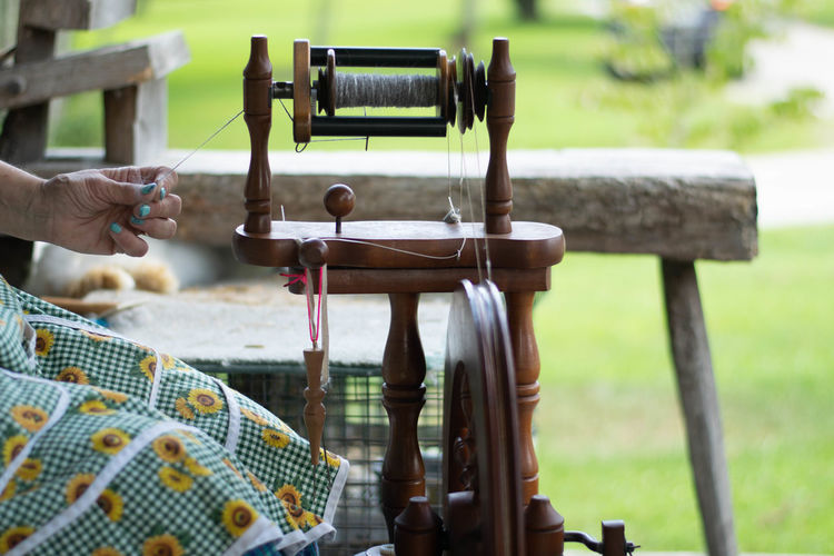 Woman spinning wool Real People Hand Human Hand Human Body Part One Person Body Part Unrecognizable Person Day Holding Focus On Foreground Finger Human Finger Lifestyles Selective Focus Outdoors Men Wood - Material Nature Table