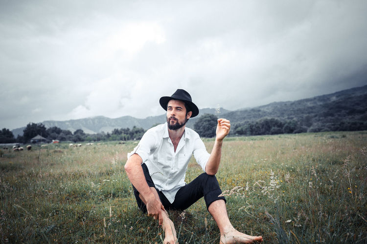 A handsome young man. Photo on nature. The guy wears a beard and medium length hair. He has an attractive face and a slim body. The man wears a black hat, a white shirt and trousers. Photo taken with daylight on a cloudy day in a mountainous area in the Caucasus. Green meadows and sky with clouds in the background. Freedom Hat Natural Sitting Adult Casual Clothing Cloud - Sky Countryside Day Field Full Length Grass Hat Land Leisure Activity Male Nature Non-urban Scene One Person Outdoors Portrait Sky Smiling Young Adult Young Men