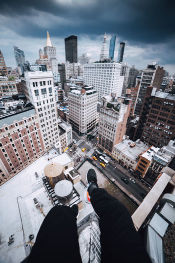 Low section of man and cityscape against sky