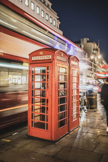 Telephone booth on footpath in city at night