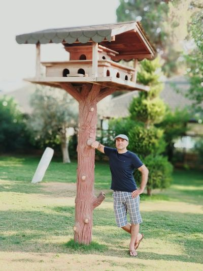 Full length of man standing by birdhouse in park