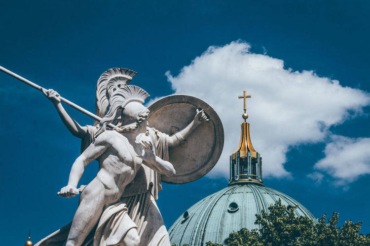 Low angle view of statue and church against sky