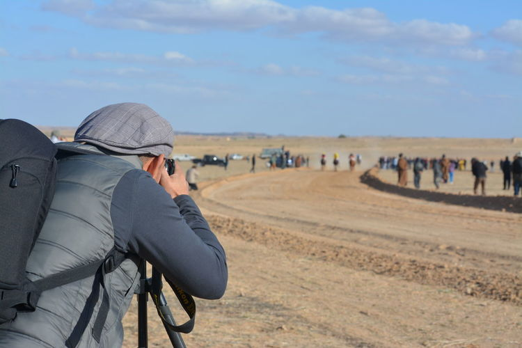 Man photographing on land against sky