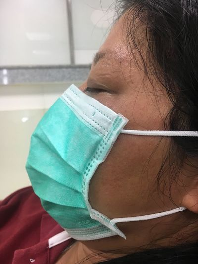 Close-up of sick woman wearing surgical mask