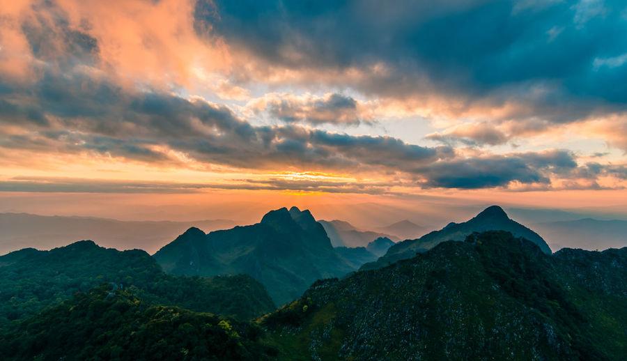 Beautiful mountain peaks topped with sky, cloud and blast horizon sun