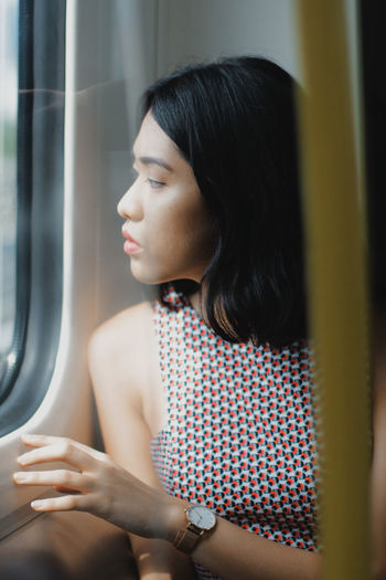 Close-up of young woman looking through window while traveling in train
