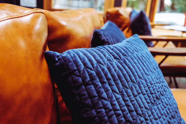 Close up detail of blue pillow on leather sofa Decor Leather Living Orange Pillow Blanket Blue Brown Business Close-up Cushion Day Decoration Decorations Decorative Focus On Foreground Furniture Furniture Details Home Interior Indoors  Interior Design Leather Sofa Living Room No People Pillow Relaxation Seat Selective Focus Sofa Softness Still Life Stuffed Textile Warm Clothing