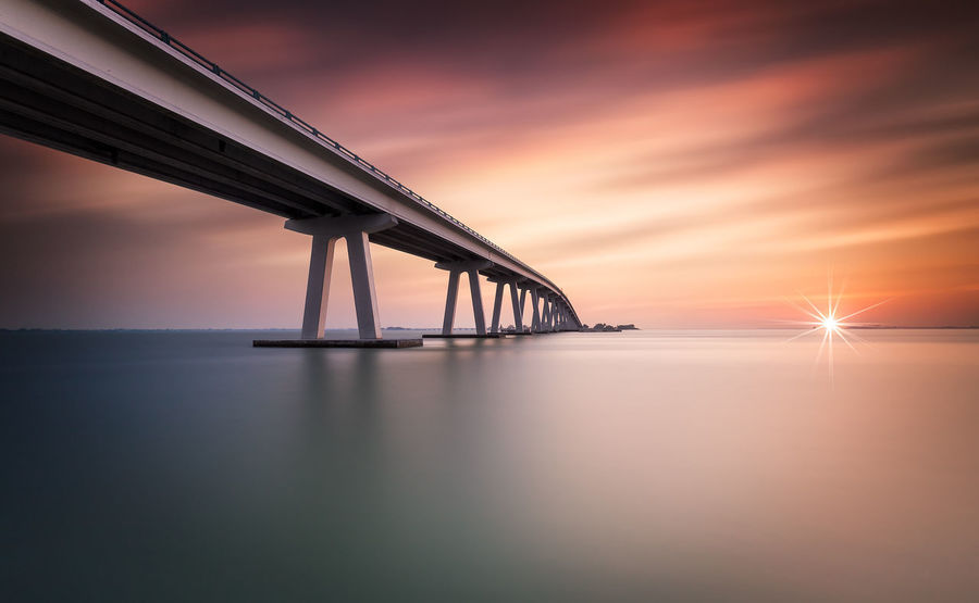 Sanibel Causeway Sunset Bridge - Man Made Structure Sky Water Connection Sun Nature Sea Beauty In Nature Built Structure No People Transportation Architecture Outdoors Waterfront Tranquility Suspension Bridge Scenics Horizon Over Water Day Florida Florida Sunset USA USA Photos Fort Myers