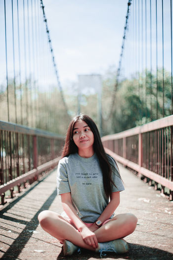 Portrait of smiling young woman sitting on footbridge against sky