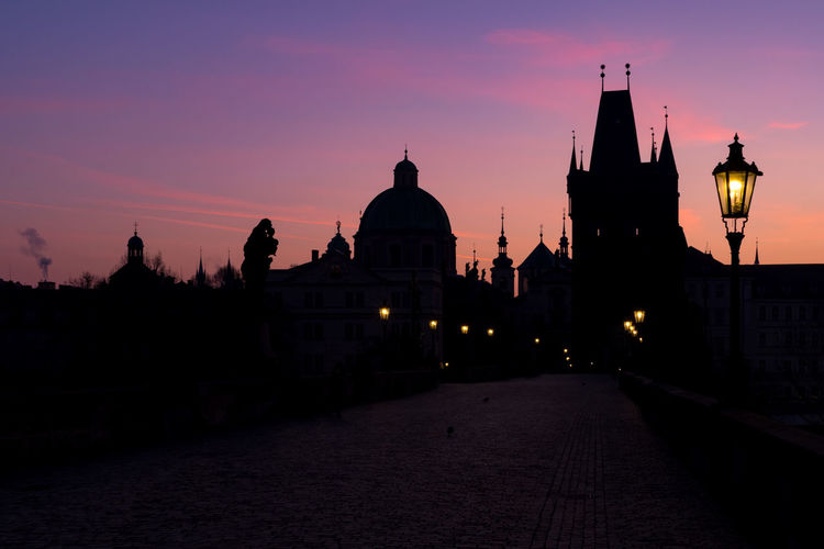 Silhouette of towers of old town in prague, view from illuminated charles bridge during sunrise