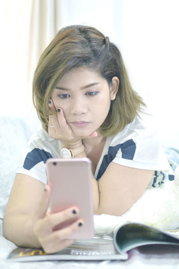 Young Woman Using Mobile Phone Over Magazine At Home