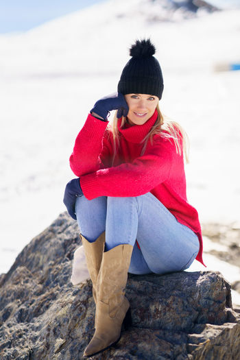 Woman sitting on rock at beach during winter