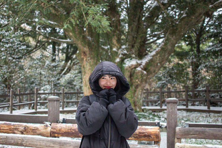 Portrait of young woman standing in park during winter