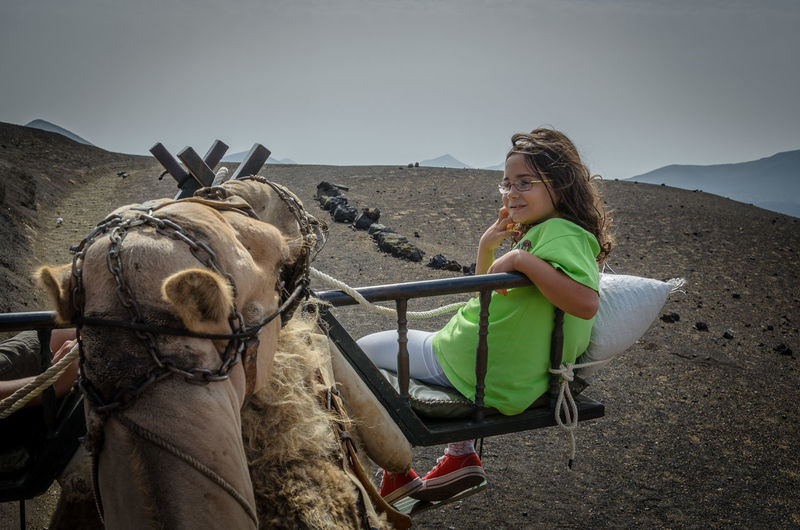 Side view of girl riding on camel at desert against clear sky