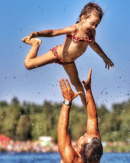 Cropped Image Of Man Catching Daughter Against Sky