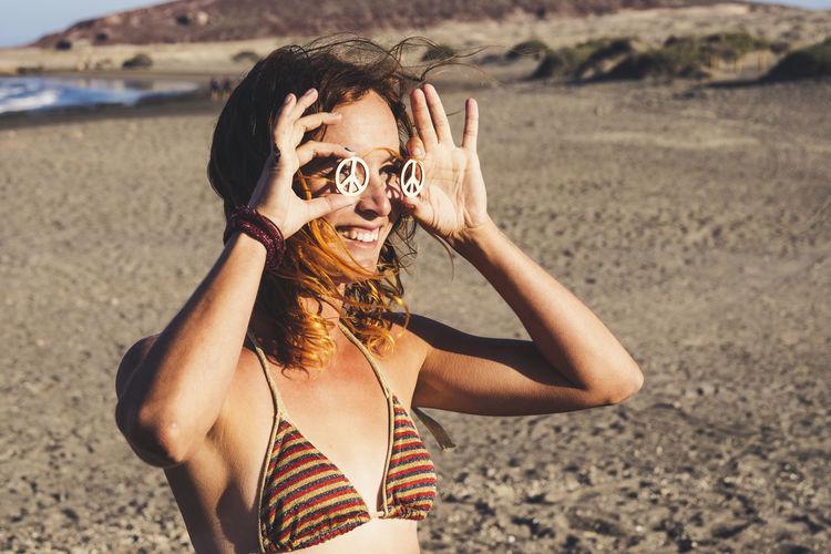 Portrait of man wearing sunglasses standing on beach