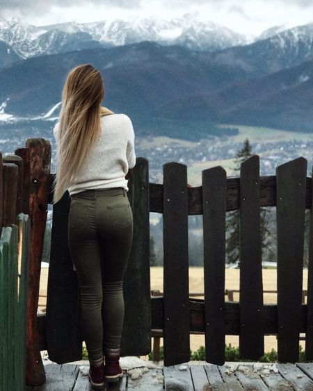 Rear view of woman standing by railing against mountains