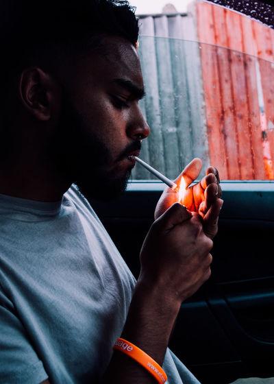 Man lighting cigarette in car