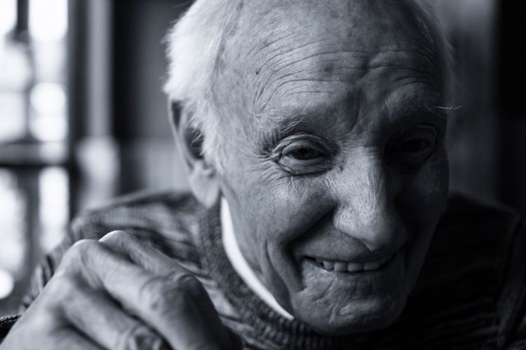 Close-Up Portrait Of Smiling Senior Man At Home