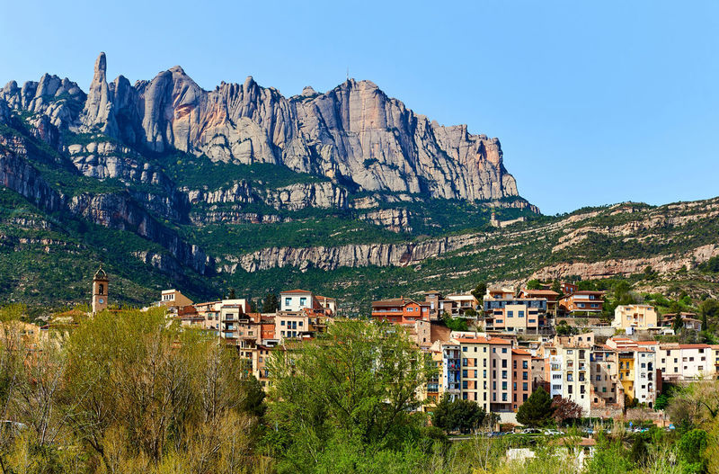 Scenic view of town against montserrat mountains against clear sky