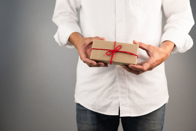 Midsection of man holding box against white background