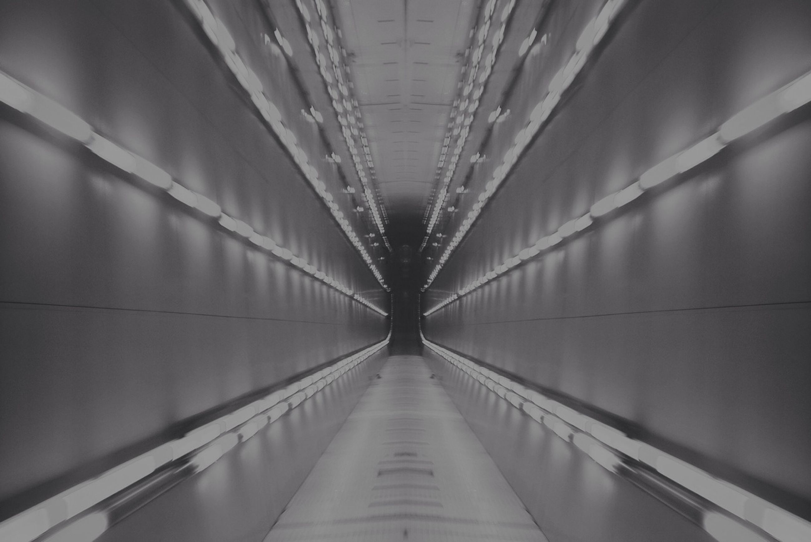 indoors, ceiling, architecture, built structure, diminishing perspective, the way forward, lighting equipment, low angle view, illuminated, pattern, building, vanishing point, wall - building feature, in a row, no people, corridor, modern, directly below, hanging, railing