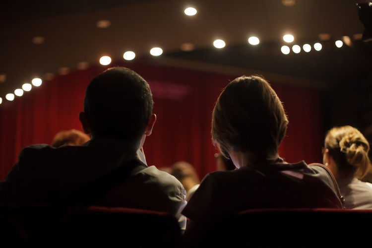 audience at theater play Arts Culture And Entertainment Adult Indoors  Group Of People Women Men Stage Theater People Illuminated Audience Auditorium Lighting Equipment Movie Theater Sitting Enjoyment Watching Light Stage Play Show Interior Red Scene Unrecognizable Back