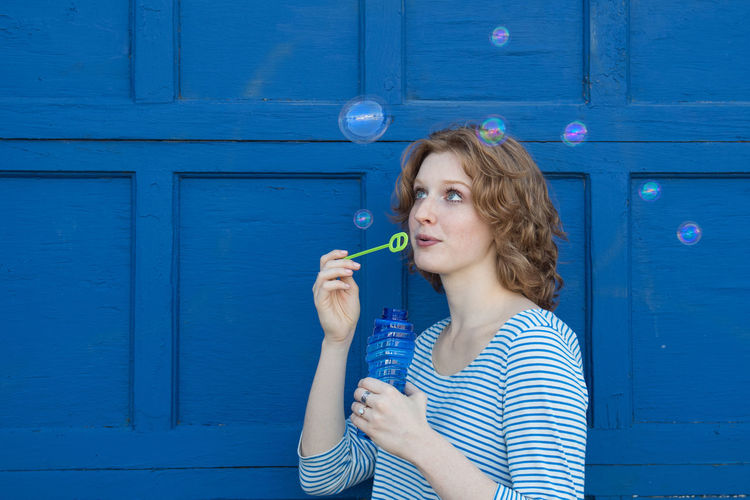 Fun with bubbles Blue Bubble Wand Curly Hair Day Door Front View Holding One Person Outdoors Portrait Young Adult