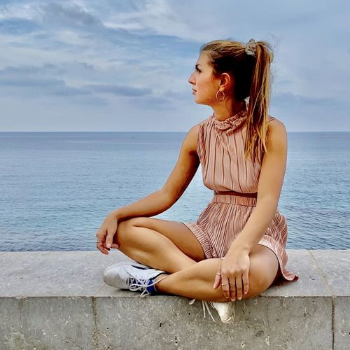 Young woman sitting by sea against sky