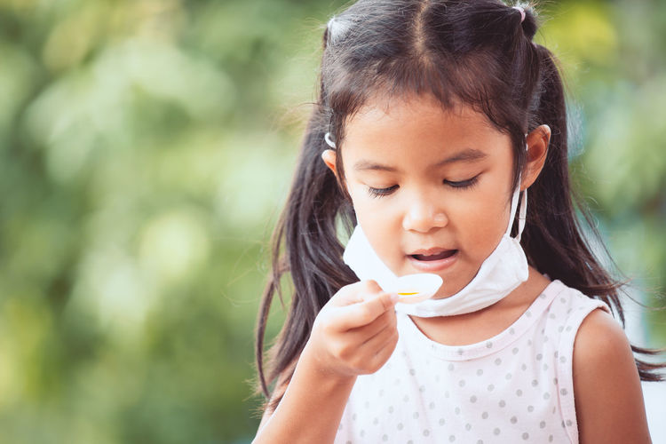 Close-up of girl taking syrup in spoon