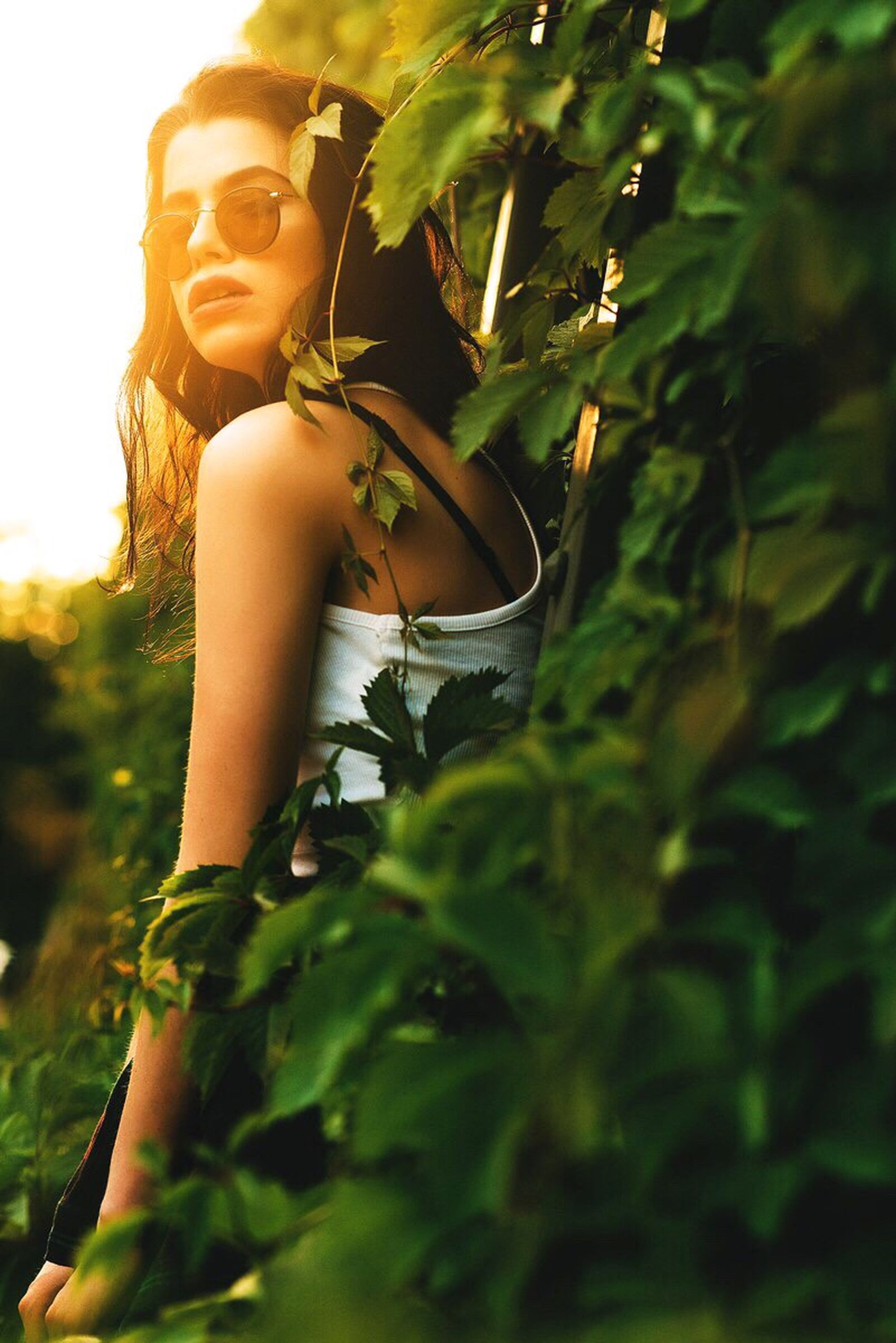 lifestyles, leaf, young adult, growth, plant, leisure activity, freshness, young women, focus on foreground, green color, close-up, holding, tree, standing, nature, sunlight, casual clothing, front view