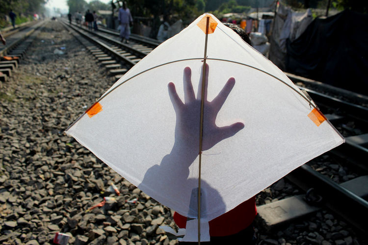 Close-Up Of Man With Kite Standing On Railroad Track