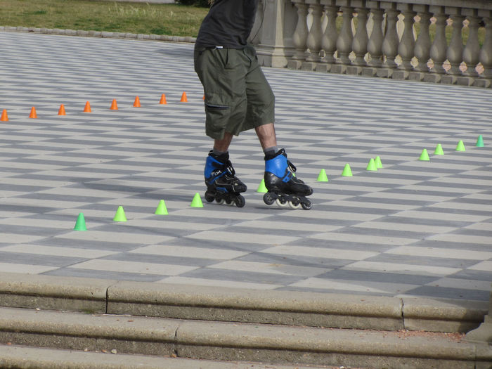 Low section of man skating on tiled floor