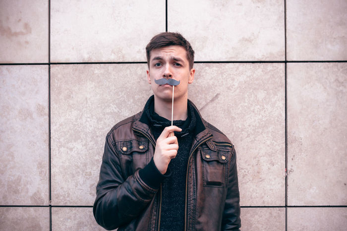 Teenagers posing with party props Adult Adults Only Beard Caucasian Day Front View Leisure Activity Looking At Camera Movember Mustache One Man Only One Person Only Men Outdoors Party People Portrait Props Standing Teenager Wall Young Adult