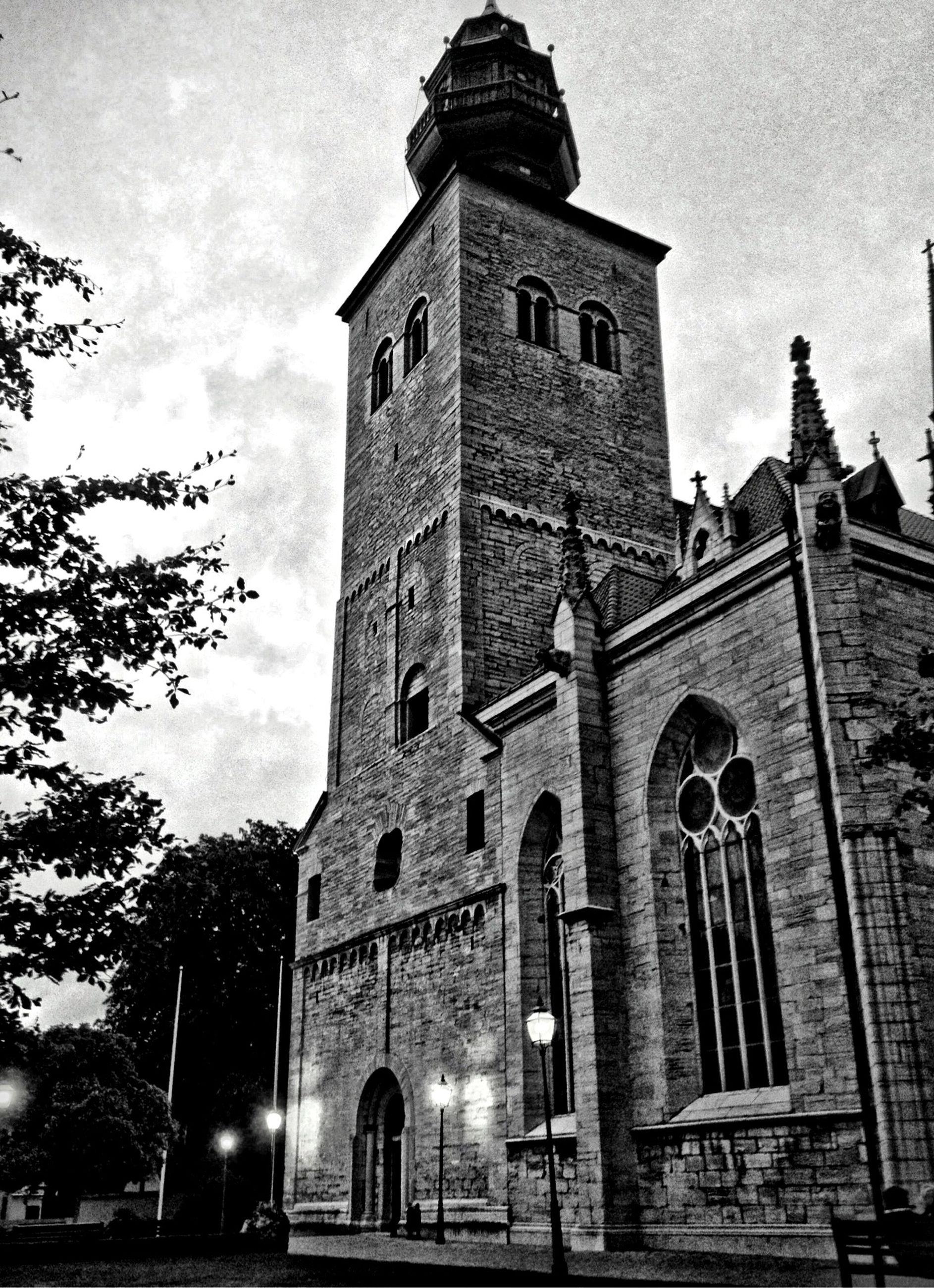architecture, building exterior, built structure, low angle view, sky, church, tree, street light, facade, history, old, religion, window, outdoors, bare tree, building, exterior, place of worship, arch