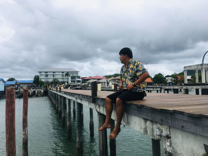Man sitting on pier over sea against cloudy sky