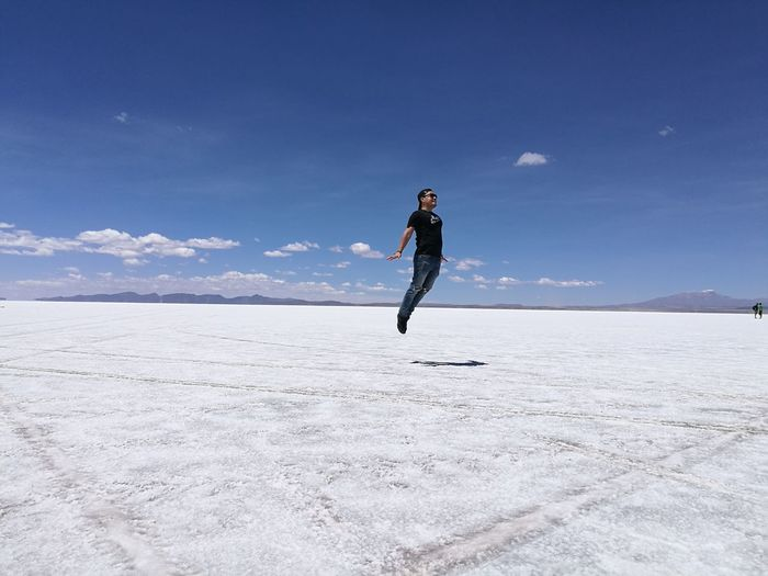 Young man levitating on salt flat against blue sky at salar de uyuni