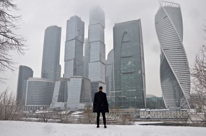 Rear view of man standing against skyscrapers during snowfall