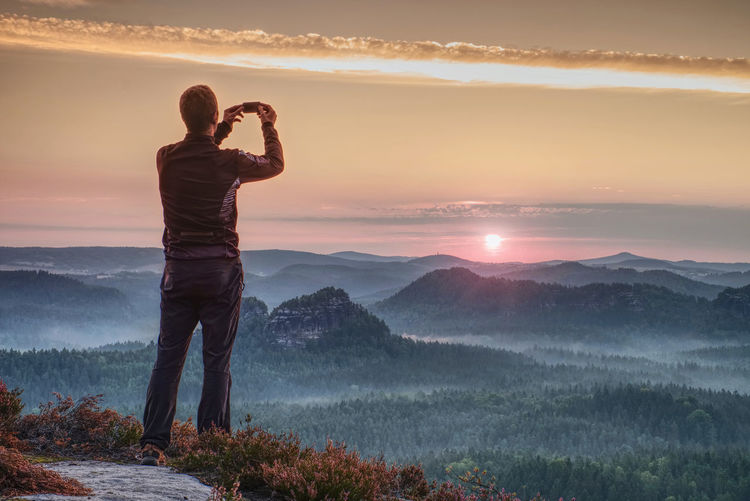 Man holding camera at eyes on mountain and watching sunset.