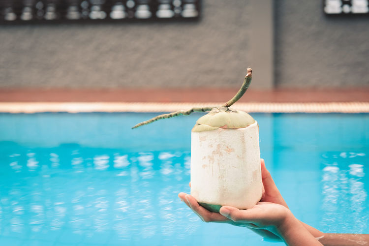 Person holding ice cream against swimming pool