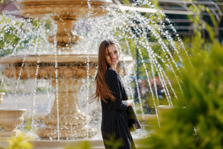 Smiling woman standing against water fountain