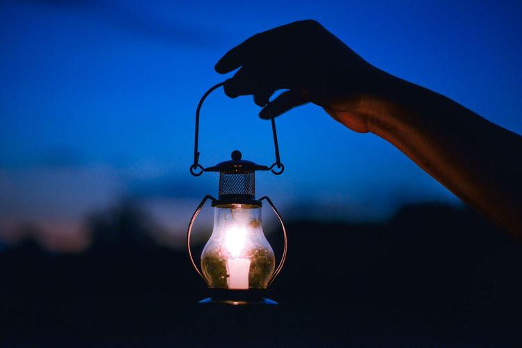 Close-up of hand holding illuminated lantern against sky at night