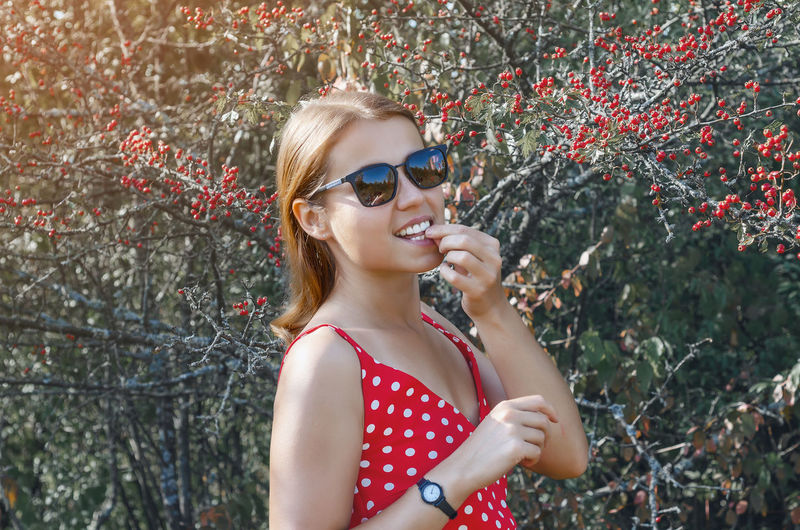 Young woman near bush with red hawthorn berries. smile, natural beauty