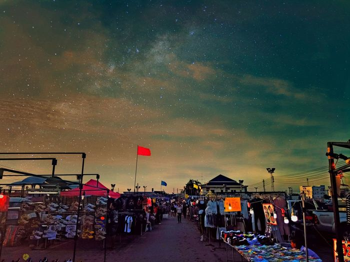 People at market stall against sky at night