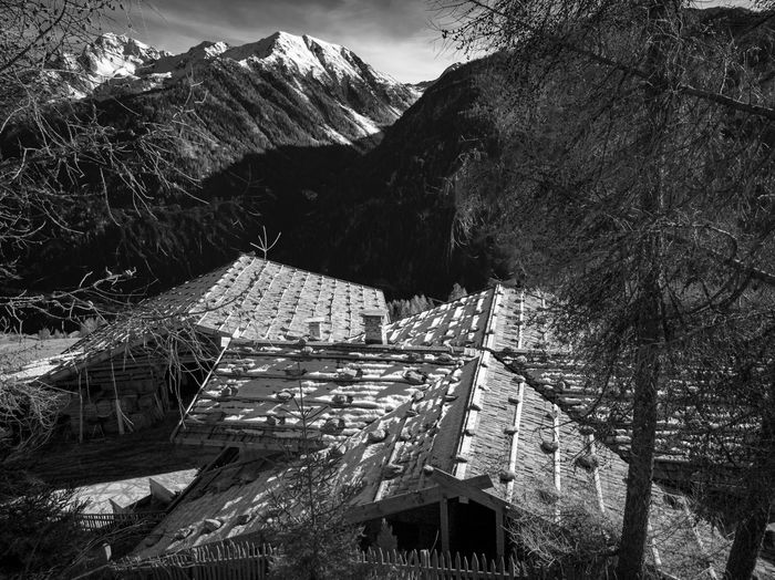 Coming down on Christmas 2018 from Mutegg, in Val Último (Ultental), I passed these farms. You could only see the roofs, and it looked like if the roofs were staying together to build a safe unit against the dangers, fierceness and unpredictability of nature. I imagined all the people living and having lived in there. Did they feel protected and safe? How many times must they have rebuilt these roofs after a storm or an avalanche? I wish all of us a protected and safe Friday 🌹 Bnw_friday_eyeemchallenge Bnw_roofs Ultental EyEm Selects Myhikes Hiking Alpine Landscape Alpine Hiking Outdoors Beauty In Nature Alto Adige South Tyrol, Italy South Tyrol Mountain Range Outdoor Activities Snowcapped Mountain Val último Tree Agriculture Rural Scene Mountain Sky