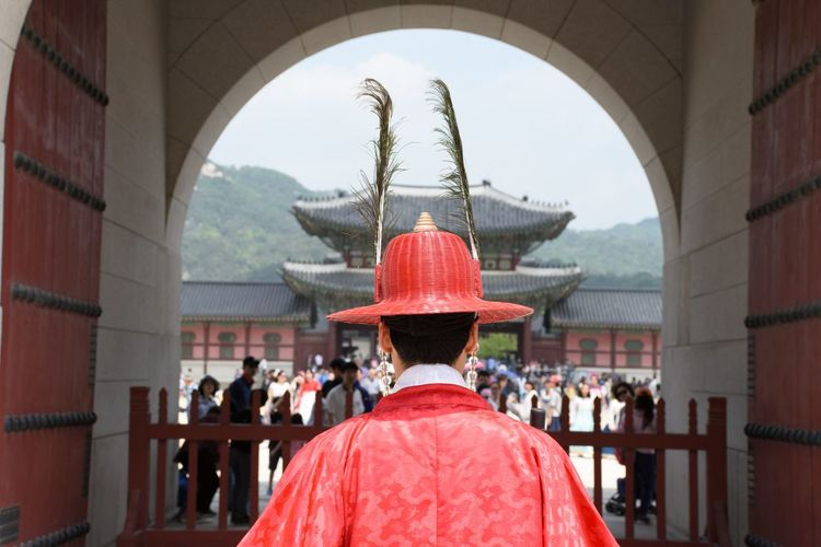 Rear View Of Man In Traditional Clothing Standing Against Shrine
