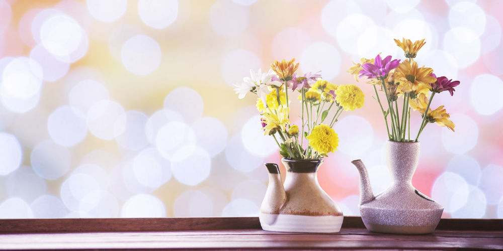 Flowers in kettle on table